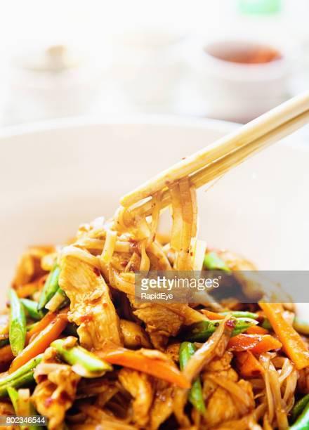 Chopsticks lift mouthful of Thai stir-fried chicken dish