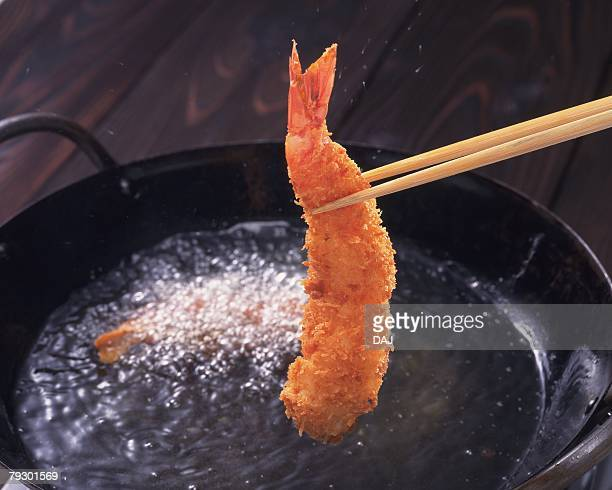 Chopsticks picking fried shrimp out of cooking oil pan, high angle view, differential focus