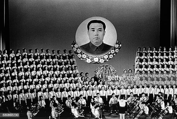 A choral performance takes place under a large picture of the North Korean Communist dictator Kim Il Sung