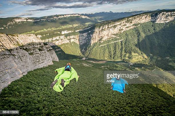 Two wingsuiters equipped with black blue and yellow wingsuits about to jump and fly in the Bourne Gorges Vercors Regional Natural Park between...