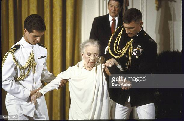 Choregrapher Agnes DeMille being escorted by Marine and Navy Personnel after accepting the National Medal of Arts from President Ronald W Reagan