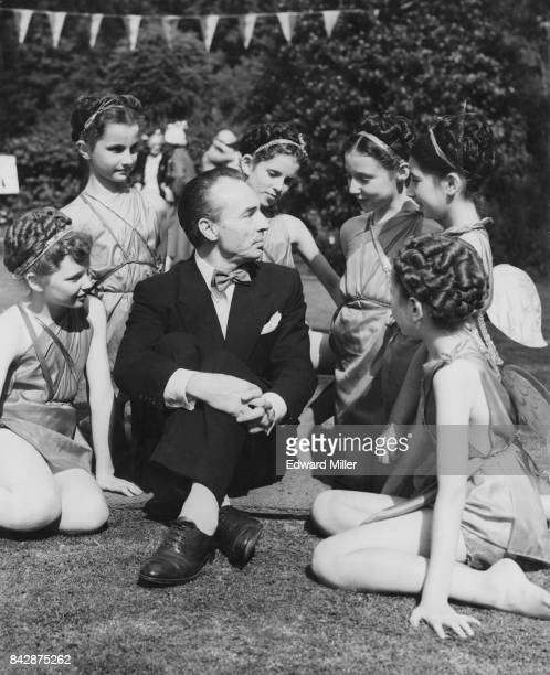 Choreographer George Balanchine Artistic Director of the New York City Ballet chats to pupils from the Royal Academy of Dancing during a garden party...