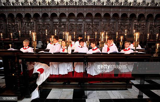 A chorister in the choir of King's College Cambridge retrieves his song sheet from the floor during a rehearsal of their Christmas Eve service of 'A...