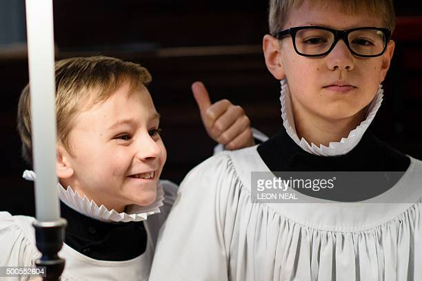 A chorister of St Paul's cathedral gives a thumbs up as they rehearse in the quire of the cathedral in central London on December 9 2015 The...