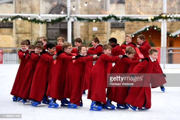 Choristers take to the ice in their cassocks to enjoy ice skating on the rink beside the Winchester cathedral on November 20 2019 in Winchester...