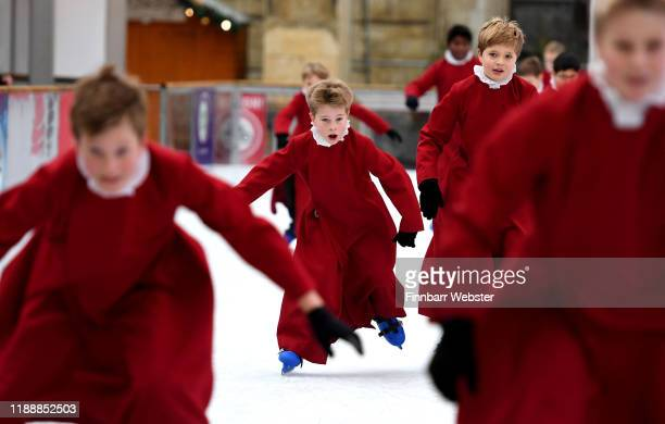 Choristers take to the ice in their cassocks to enjoy ice skating on the rink beside the Winchester cathedral on November 20, 2019 in Winchester,...