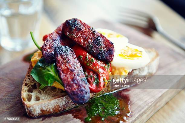 chorizo and egg tartine with pesto on wooden board
