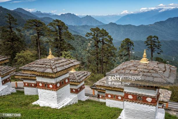 chortens and mountains at dochula pass, bhutan - thimphu stock pictures, royalty-free photos & images