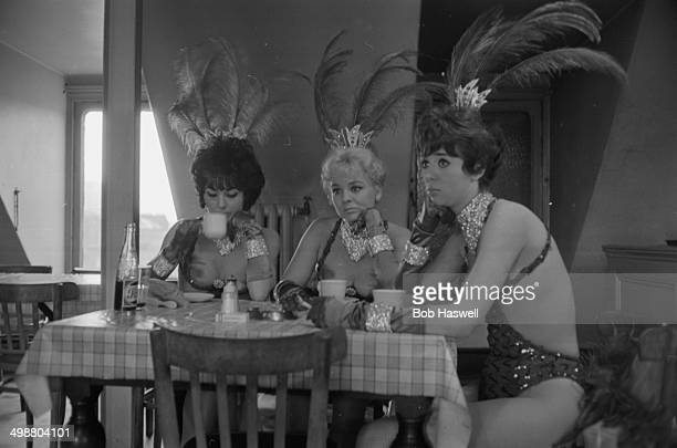 Chorus girls Mandie Mayer Pat Patterson and Alexis Holmes drinking tea in full showgirl costume backstage Windmill Theatre London 1964