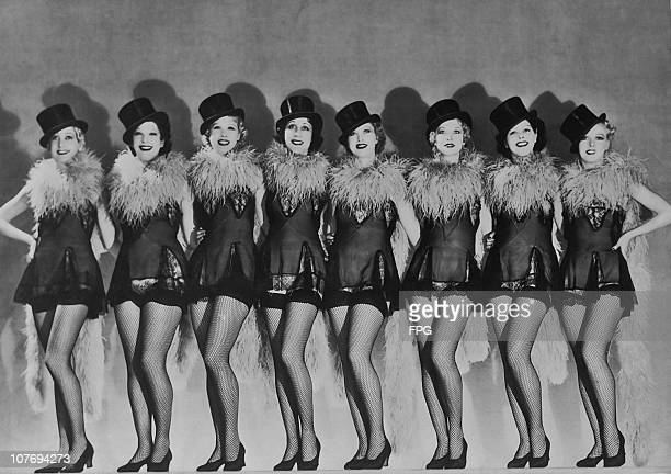 A chorus line of showgirls in top hats feather boas and fishnet stockings circa 1935