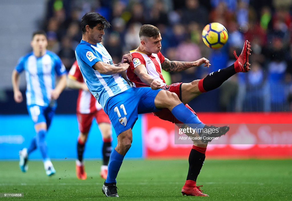 Chory Castro of Malaga CF (L) competes for the ball with Pablo Maffeo of Girona FC (R) during the La Liga match between Malaga and Girona at Estadio La Rosaleda on January 27, 2018 in Malaga, .