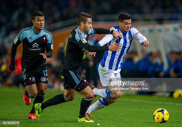 Chory Castro of Real Sociedad competes for the ball with Hugo Mallo and Rafinha of Celta de Vigo during the La Liga match between Real Sociedad de...