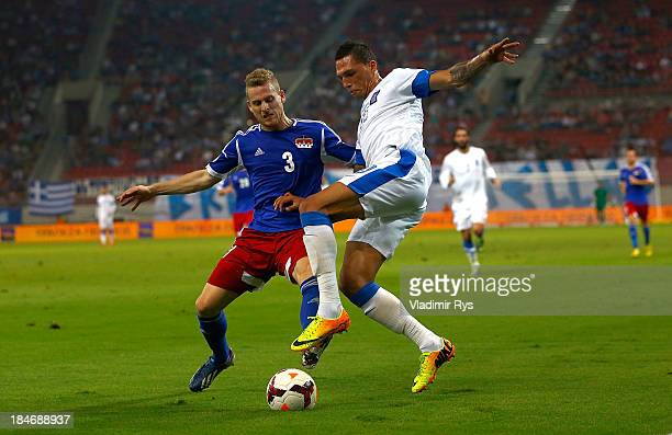 Chose Cholebas of Greece and Yves Oehri of Liechtenstein battle for the ball during the group G FIFA 2014 World Cup Qualifier match between Greece...