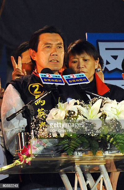 Chou Meiching wife of Taiwan's presidential candidate Ma Yingjeou from the opposition Kuomintang party whispers to her husband as he delivers his...