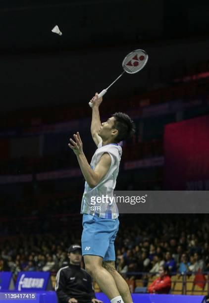 Chou Tien Chen of Taiwan hits a return against Kenta Nishimoto of Japan during their men's singles quarterfinal match at the 2019 Badminton Asia...