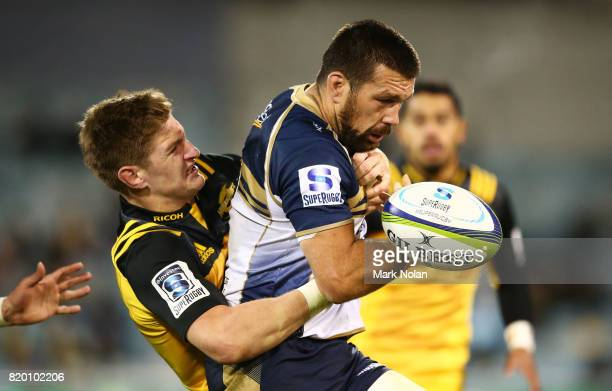 Chris Alcock of the Brumbies loses the ball in a tackle by Jordie Barrett of the Hurricanes during the Super Rugby Quarter Final match between the...