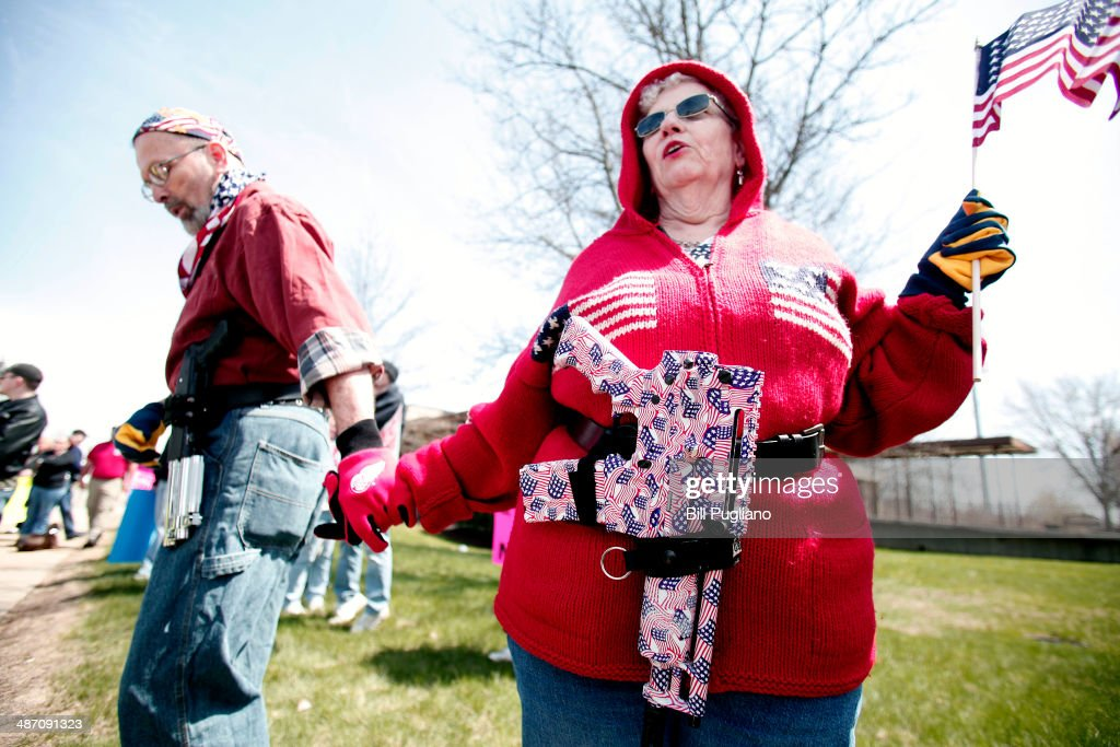 Chris (right) and Marty Welch of Cadillac, Michigan, carry decorated Olympic Arms .223 pistols at a rally for supporters of Michigan's Open Carry law April 27, 2014 in Romulus, Michigan. The march was held to attempt to demonstrate to the general public what the typical open carrier is like.