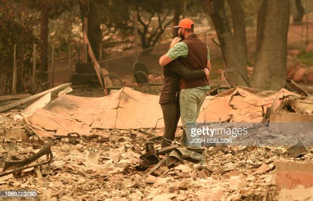 TOPSHOT Chris and Nancy Brown embrace while looking over the remains of their burned residence after the Camp fire tore through the region in...