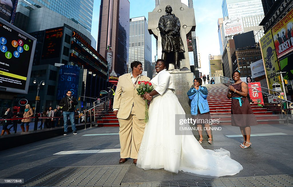 Chris (R) and Renee Wiley get ready to pose for a wedding photo on Times Square in New York, December 12, 2012. Same-sex marriage in New York state became legal on July 24, 2011. Couples are flocking to tie the knot on 12/12/12, sparking a wedding boom on the century's last sequential dates seen as auspicious by some to guarantee a happy marriage. AFP PHOTO/Emmanuel DUNAND