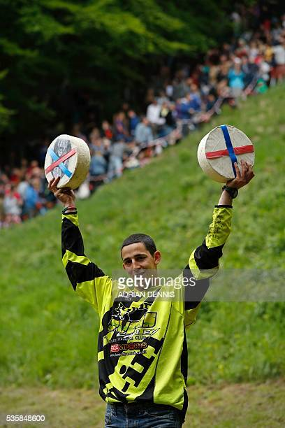 Chris Anderson poses for pictures with his prize cheeses after winning his second race during the annual Cooper's Hill cheese rolling competition...