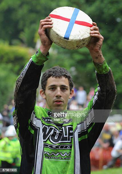 Chris Anderson winner of the first men's race holds up a Double Gloucester Cheese at the bottom of Cooper's Hill during the annual Bank Holiday...