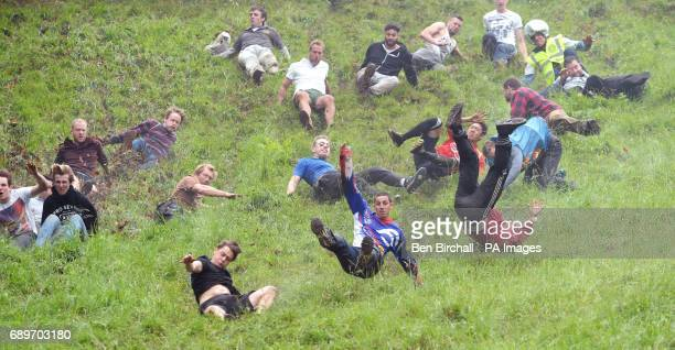 Chris Anderson wins the first race during the annual unofficial cheese rolling at Cooper's Hill in Brockworth Gloucestershire where a cheese has been...