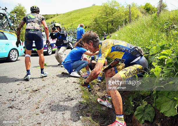 Chris Anker Sorensen of Denmark and TinkoffSaxo ties to stand after being involved in a crash during the tenth stage of the 2014 Giro d'Italia a...