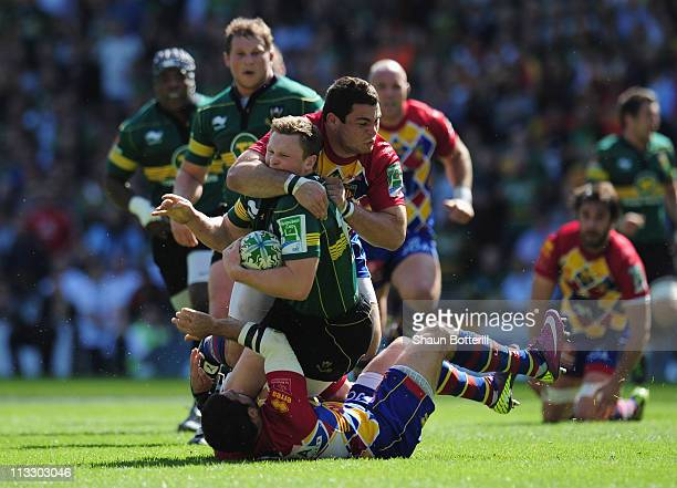 Chris Ashton of Northampton Saints is tackled by Guilhem Guirado and Julien Candelon of USA Perpignan during the Heineken Cup SemiFinal match between...
