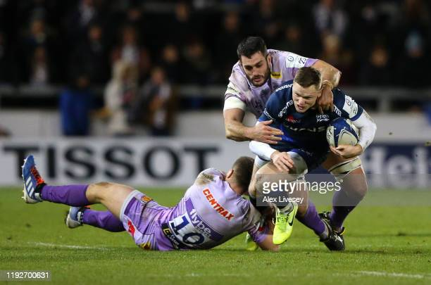 Chris Ashton of Sale Sharks is tackled by Dave Dennis and Joe Simmonds of Exeter Chiefs during the Heineken Champions Cup Round 3 match between Sale...