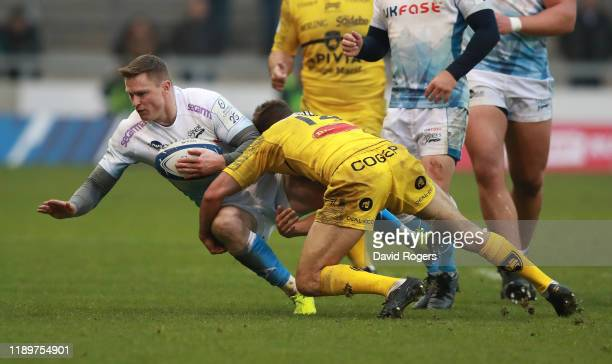 Chris Ashton of Sale Sharks is tackled by Vincent Rattez during the Heineken Champions Cup Round 2 match between Sale Sharks and La Rochelle at AJ...