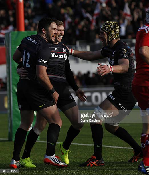Chris Ashton of Saracens celebrates scoring a try with Brad Barritt and Kelly Brown during the European Rugby Champions Cup pool one match between...