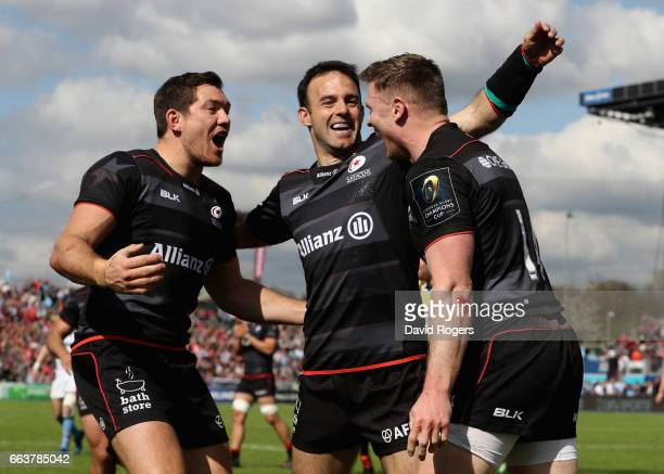 Chris Ashton of Saracens is congratulated by team mates Alex Goode and Neil de Kock after scoring his second try during the European Rugby Champions...
