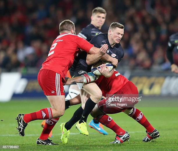 Chris Ashton of Saracens is tackled by Duncan Casey and BJ Botha during the European Rugby Champions Cup match between Munster and Saracens at...
