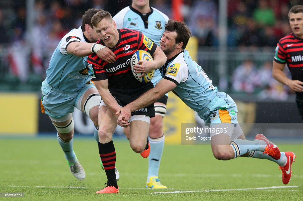 Chris Ashton of Saracens is tackled by Phil Dowson and Ben Foden (R) during the Aviva Premiership semi final match between Saracens and Northampton Saints at Allianz Park on May 12, 2013 in Barnet, England.
