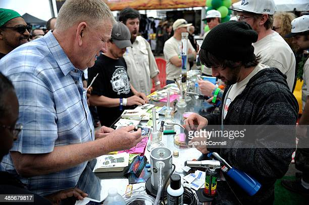 Chris Bagley left loads up a dab for a client at the Gaia booth during the High Times Cannabis Cup at Denver Mart in Denver Colorado on April 19 2014...