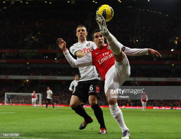 Chris Baird of Fulham looks on as Robin van Persie of Arsenal controls the ball during the Barclays Premier League match between Arsenal and Fulham...