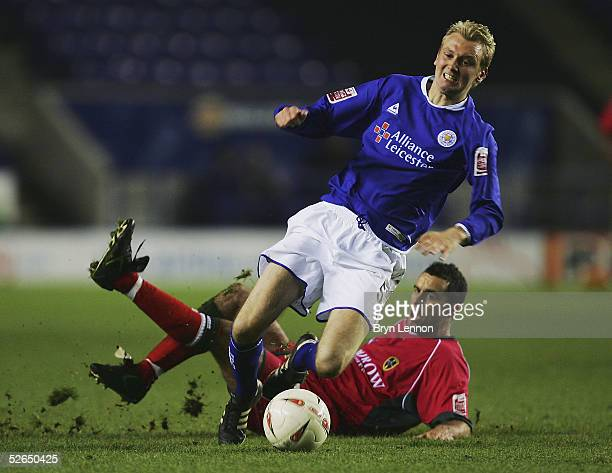 Chris Barker of Cardiff City tackles Stephen Hughes of Leicester City during the CocaCola Football League Championship match between Leicester City...