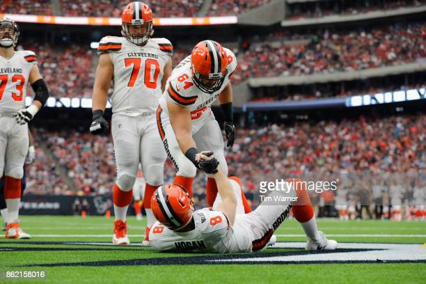 Chris Barker of the Cleveland Browns helps Kevin Hogan to his feet after being tackled in the end zone during the third quarter against the Houston...