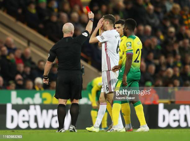 Chris Basham of Sheffield United is shown a red card by referee Simon Hooper which is later changed to a yellow card by VAR during the Premier League...
