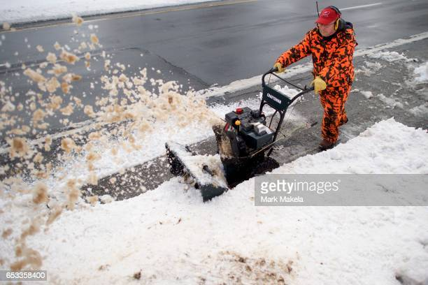 Chris Benyo clears his driveway with a snowblower March 14 2017 in Douglassville Pennsylvania A blizzard is forecast to bring more than a foot of...