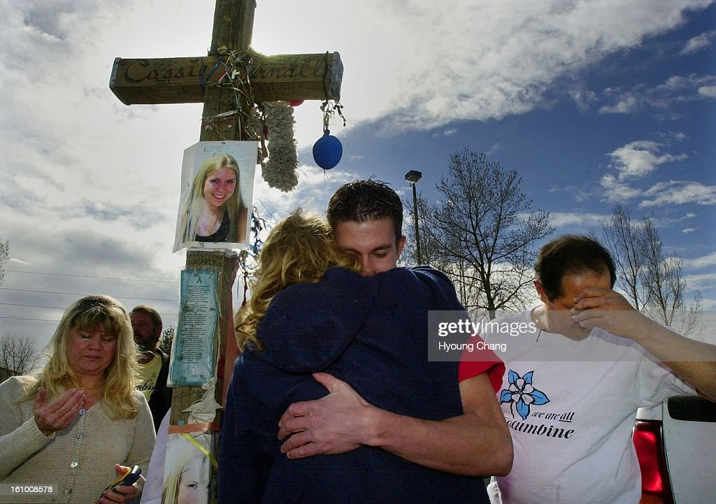Chris Bernall, brother of Columbine high school shooting victim Cassie Bernall, center top, hugs Rhonda Erdman of Morrison during the Columbine two-year anniversary at Clement Park on Friday. Chris set the Cassie's cross up by the help of Donna Taylor of  : News Photo
