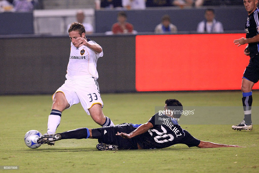 Chris Birchall #33 of the Los Angeles Galaxy atteampts to get a ball around the defense of Ramon Sanchez #20 of the San Jose Earthquakes during their MLS game at The Home Depot Center for a loose ball on October 24, 2009 in Carson, California.