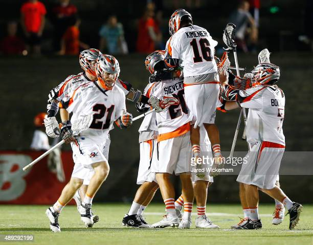 Chris Bocklet of the Denver Outlaws is mobbed by teammates after scoring the game-winning goal in overtime against the Boston Cannons at Harvard...