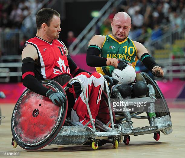 Chris Bond of Australia is challenged by Fabien Lavoie of Canada to the ball during the Wheelchair Rugby match between Australia and Canada on day 7...