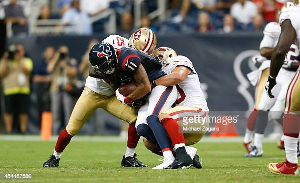 Chris Borland and Jimmie Ward of the San Francisco 49ers tackles DeVier Posey of the Houston Texans during the game at Reliant Stadium on August 28...