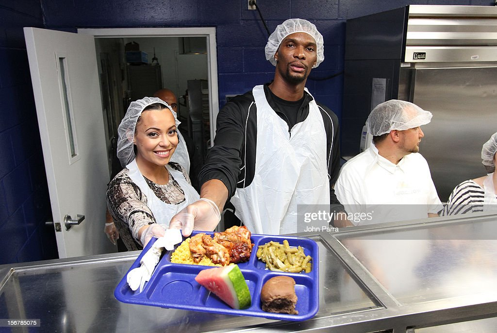 Chris Bosh and Adrienne Bosh attend the 2nd year with the Chapman Partnership to help feed the local families of Miami this Thanksgiving at Chapman Partnership on November 20, 2012 in Miami, Florida.