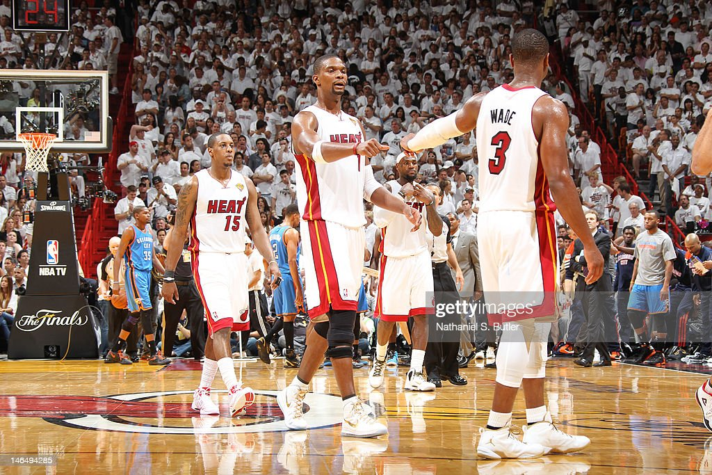 Chris Bosh #1 and Dwyane Wade #3 of the Miami Heat celebrate a win over the Oklahoma City Thunder in Game Three of the 2012 NBA Finals at American Airlines Arena on June 17, 2012 in Miami, Florida.