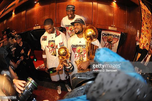 Chris Bosh and Dwyane Wade pose with LeBron James of the Miami Heat as he holds both trophies in a locker room after winning Game Five of the 2012...