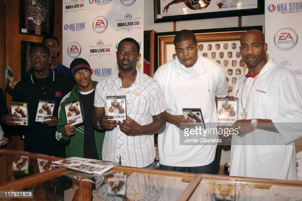 Chris Bosh Dwyane Wade Nick Cannon Brian McKnight Josh Smith and Vince Carter hold the EA Sports NBA Live 06 game at the exclusive premiere of EA...