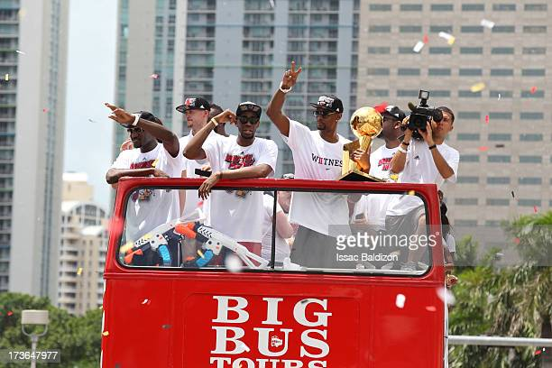 Chris Bosh holds the Larry O'Brien Trophy next to teammates Joel Anthony and Norris Cole of the Miami Heat during the NBA championship parade through...